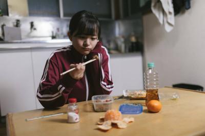 食べ物に注意しながら食べる女性